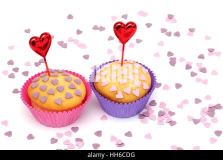 Two cupcakes with little pink and purple hearts - Stock Photo