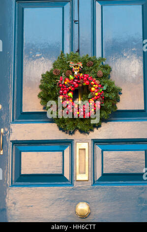 Christmas wreath  with berries on front door - Stock Photo