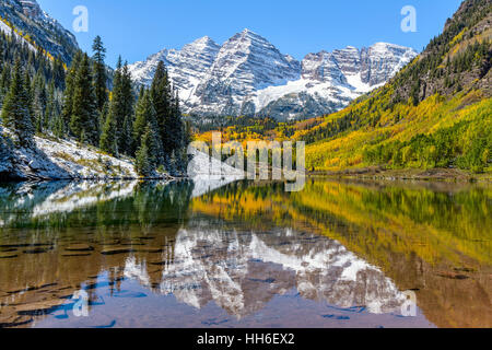 Maroon Bells and Maroon Lake - A wide-angle autumn view of snow coated Maroon Bells reflecting in crystal clear - Stock Photo
