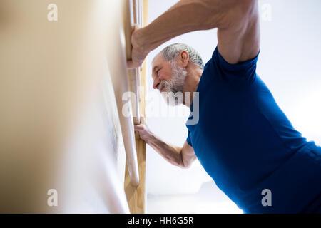 Senior man in gym exercising on wall bars. - Stock Photo