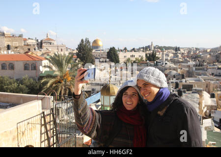 Young couple stand above Damascus Gate use a smartphone to take a selfie with the Dome of the Rock and the Old City - Stock Photo