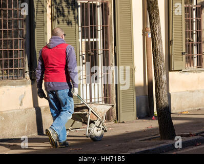 Construction worker pushing a wheelbarrow on the street - Stock Photo