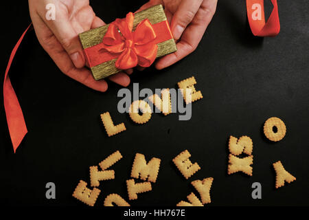 Two hands holding a gift with red ribbon with word love - Stock Photo