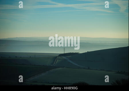 Mist over farmland during dawn on a winters day in the beautiful Sussex countryside in the South Downs National - Stock Photo