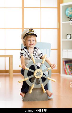 Kid dressed as a captain or sailor plays on chair as on ship in his room. Child boy rotates the wooden steering - Stock Photo