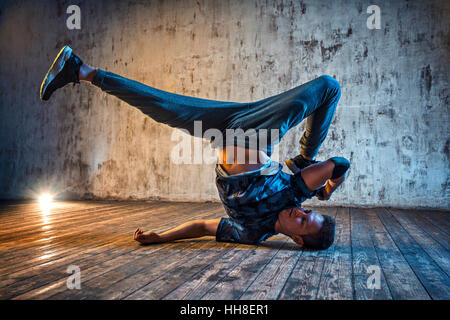 Young man break dancing on wall background - Stock Photo