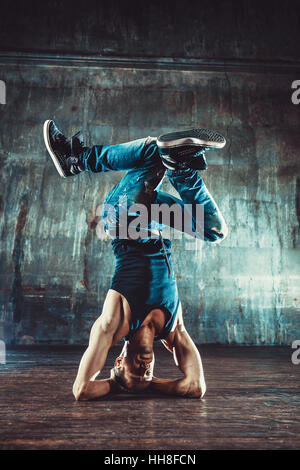 Young man break dancing on old wall background. Vintage film style colors. - Stock Photo