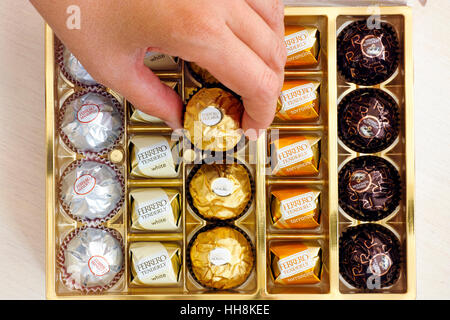 Paphos, Cyprus - November 20, 2016 Woman hand taking candy from box of Ferrero candies. - Stock Photo