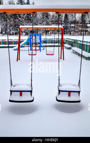 Children's playground covered with snow in winter - Stock Photo