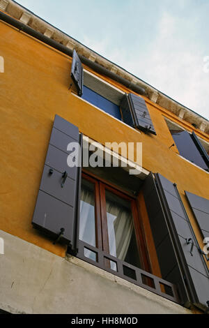Vintage wooden window shutters. Yellow facade house with wooden shutters. - Stock Photo