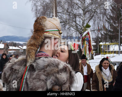 Young couple in Bulgarian folk costumes kissing oh the street during Surva celebration - Stock Photo