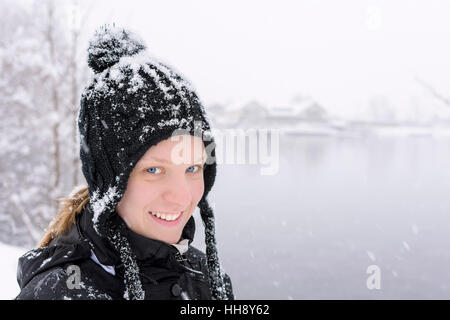 Winter Portrait of Young Woman with Blue Eyes in Knitted Black Wool Hat with Snow Flakes on the Mountain Lake and - Stock Photo