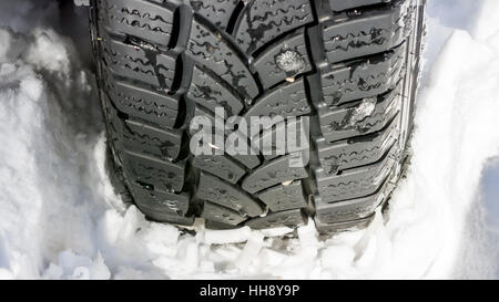 Car Tire on the Snowy Road Close Up. Winter Driving Conditions. - Stock Photo