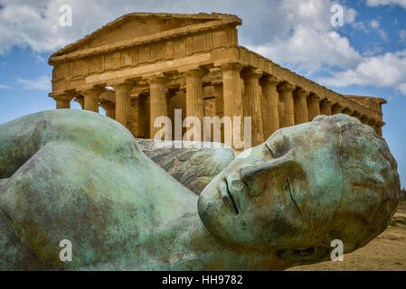 bronze statue of fallen ikaro on the background the concorde temple, Agrigento, Sicily, Italy - Stock Photo