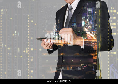 Double exposure of businessman working with tablet,  night city and night street - Stock Photo