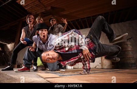 Young Asian man performs break dancing moves on cardboard - Stock Photo