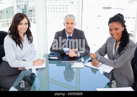 Serious director sitting at the desk and accompanied by two smiling businesswomen - Stock Photo