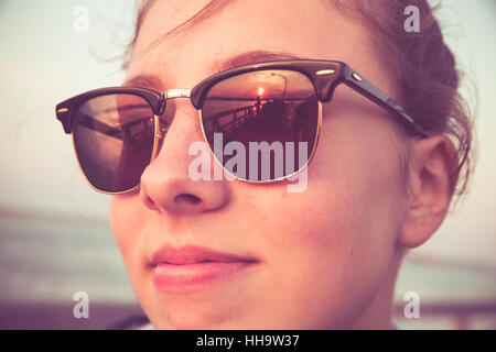 Cute teenage girl with sunset reflections in sunglasses. Image has a retro vintage filter effect - Stock Photo