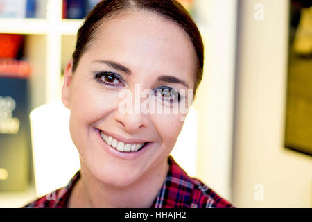 Portrait of a woman smiling, happy, looking at camera, mid aged. - Stock Photo