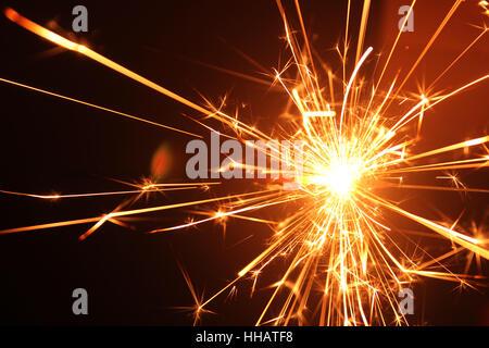a burning sparkler on black