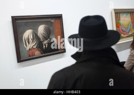 Visitor in front of the painting Les Amants (The Lovers, 1928) by Belgian surrealist artist Rene Magritte displayed - Stock Photo