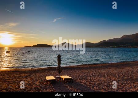 Sveti Stefan sand beach with pair of sunchairs near Budva, Montenegro. Balkans, Adriatic sea, Europe. Sunset time - Stock Photo