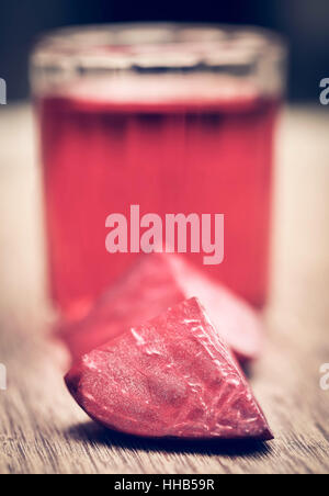 Fresh Beet with juice in glass on wooden surface - Stock Photo