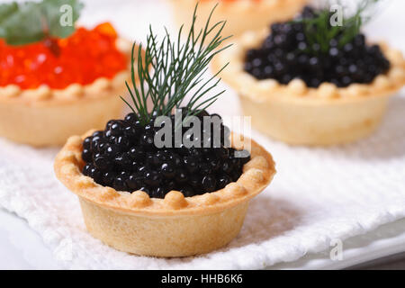 Canapes with red and black fish caviar on a plate. macro. horizontal - Stock Photo