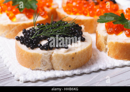 sandwiches with black and red caviar on the table macro. horizontal - Stock Photo