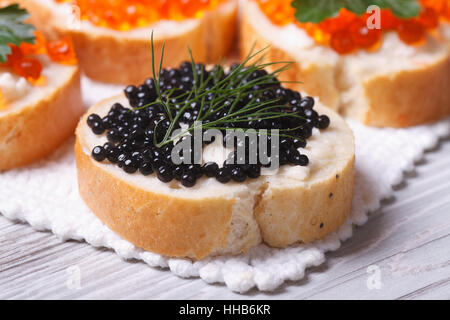 Sandwiches with black caviar fish macro on the table. horizontal - Stock Photo