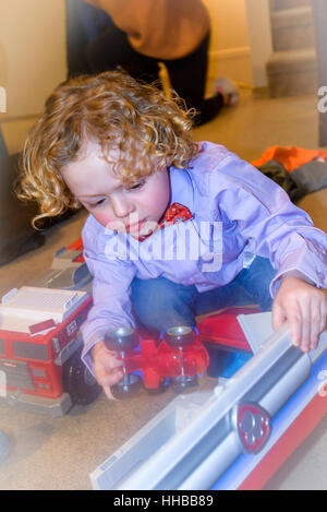 young boy playing with fire truck toy - Stock Photo