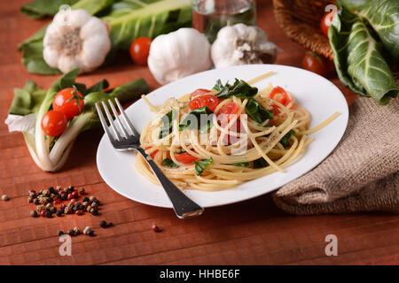 Spaghetti with chard and tomato - Italian food - Stock Photo