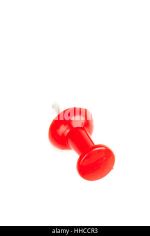 Close up of a red pushpin pierced in the wall against a white background - Stock Photo