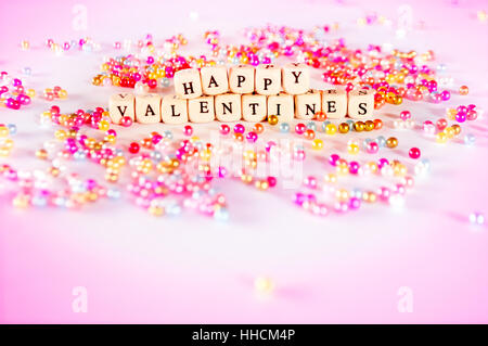 Happy Valentines text with multicolor beads with pinkish ambient. - Stock Photo