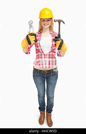 Woman wearing a safty helmet while holding tools against white background - Stock Photo
