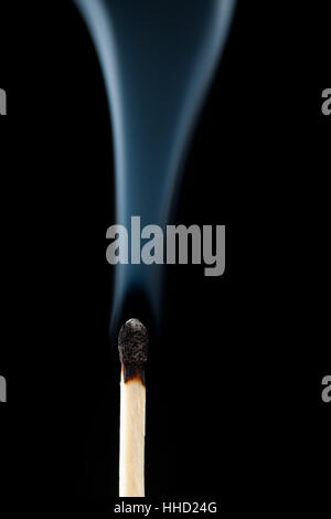 Smoking consumed match against a black background - Stock Photo