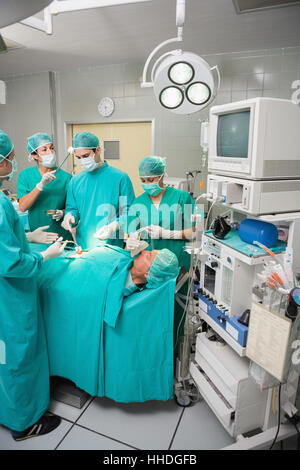 Patient lying on a medical bed undergoing an operation in an operating theatre - Stock Photo