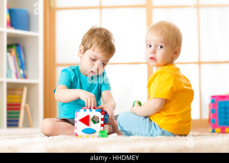 Kids playing with logical toy on soft carpet in nursery roomor kindergarten. Children arranging and sorting shapes - Stock Photo