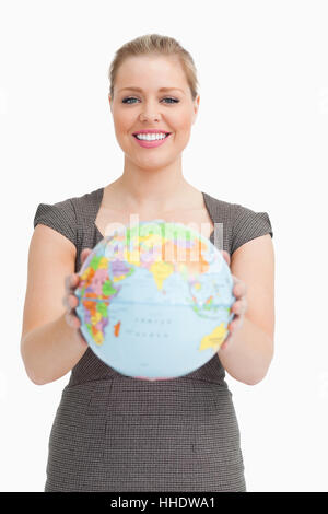 Woman showing a globe against white background - Stock Photo