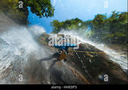 A man pauses to smile for the camera while canyoning in a waterfall, Nepal - Stock Photo