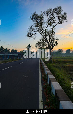 Quiet Road In Yogyakarta, Central Java, Indonesia. Rare lack of traffic during the early morning sun rise. Close - Stock Photo