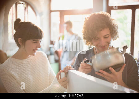 Young couple looking into pot at refrigerator - Stock Photo