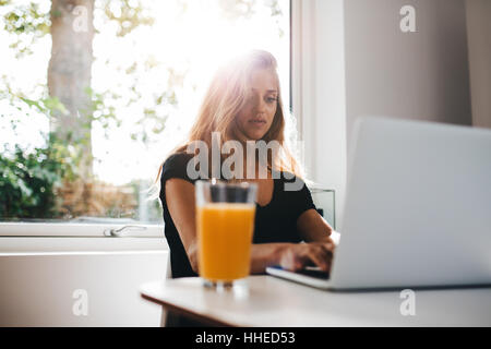 Indoor shot of female working on laptop. Woman in morning sitting in kitchen and using laptop computer. - Stock Photo