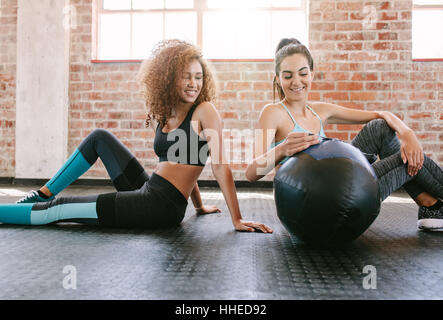Two young female friends sitting on gym floor with medicine ball. Young woman working out in gym. - Stock Photo