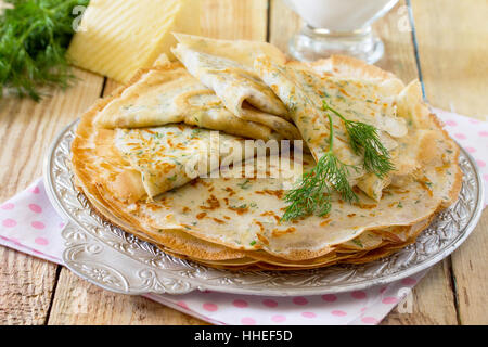 Not sweet pancakes with cheese and fresh dill on a wooden table. Breakfast, snack or brunch. Healthy food concept. - Stock Photo