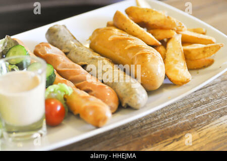 mixed sausage with French fries and vegetable - Stock Photo