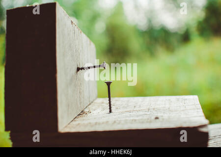 Screw screwed into a wooden Board on green background - Stock Photo