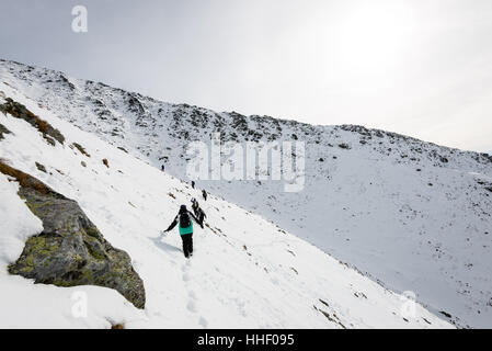 tourists enjoying high mountains in snow on a sunny day. sun and blue sky in slovakia - Stock Photo