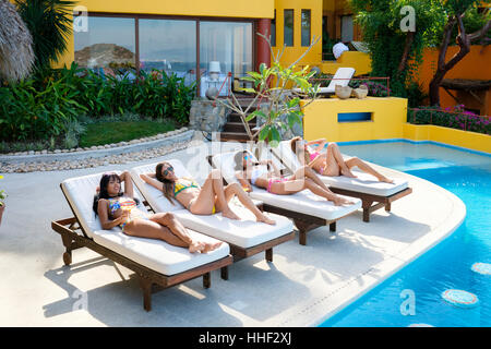 Four young women lying on deck loungers tanning next to the swimming pool of an upscale residence in Mexico - Stock Photo