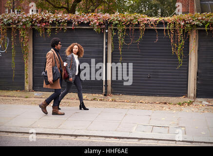 Stylish Young Couple Walking Past Garages On City Street - Stock Photo